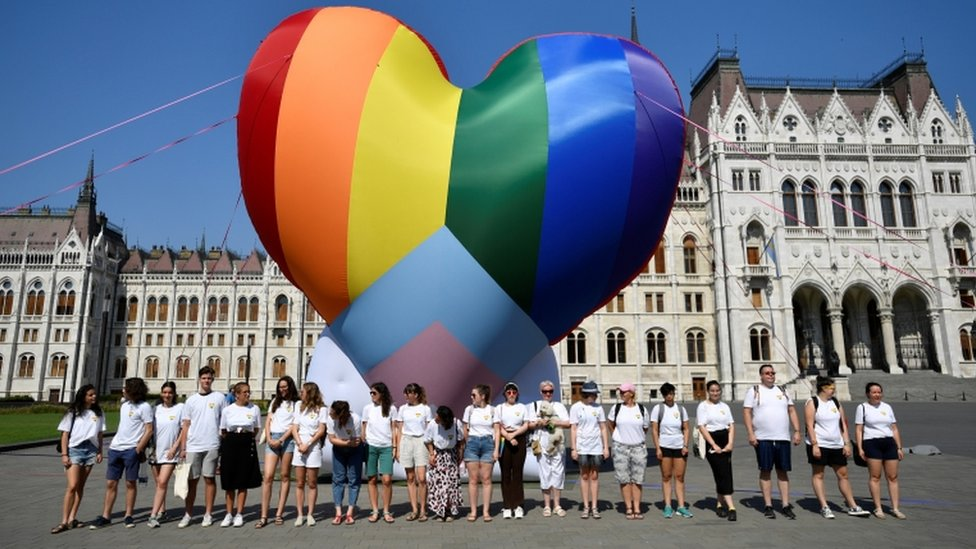 Activists gather in front of a huge heart-shaped rainbow balloon