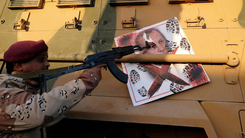 A solider loyal to Gen Hafter points his gun at the image of Turkish President Tayyip Erdogan stuck to an armoured vehicle in Benghazi - January 2020