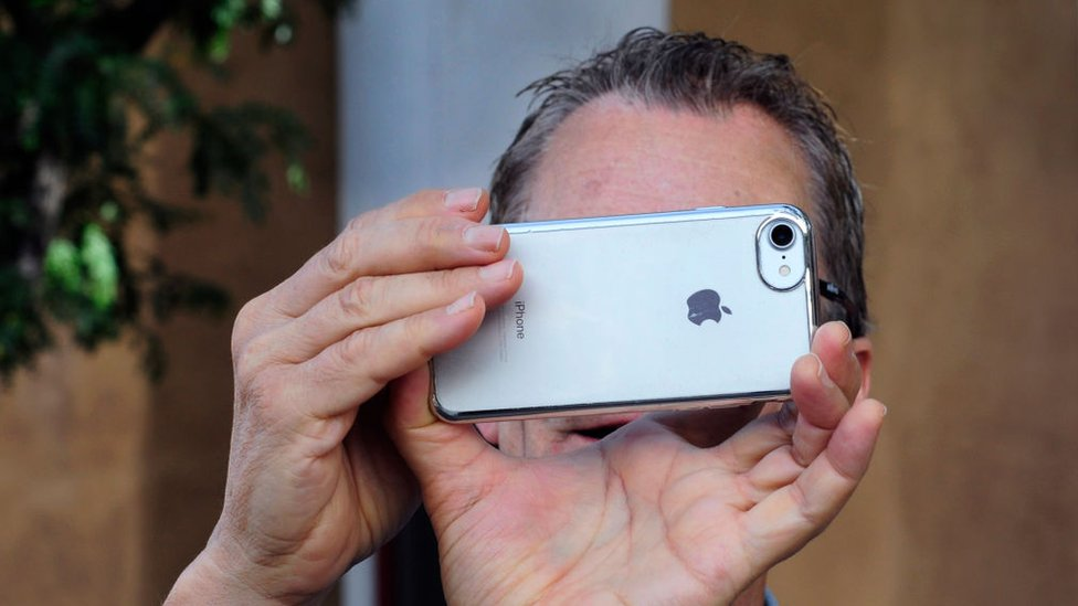 A person takes a picture with the iPhone