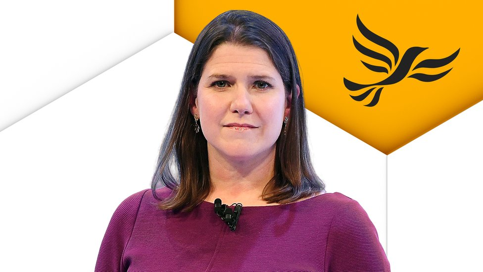 Jo Swinson in front of Lib Dem logo