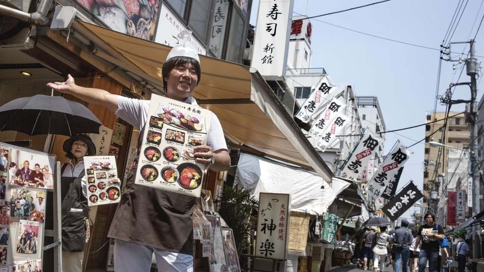 A man stands outside a seafood restaurant in Tsujiki