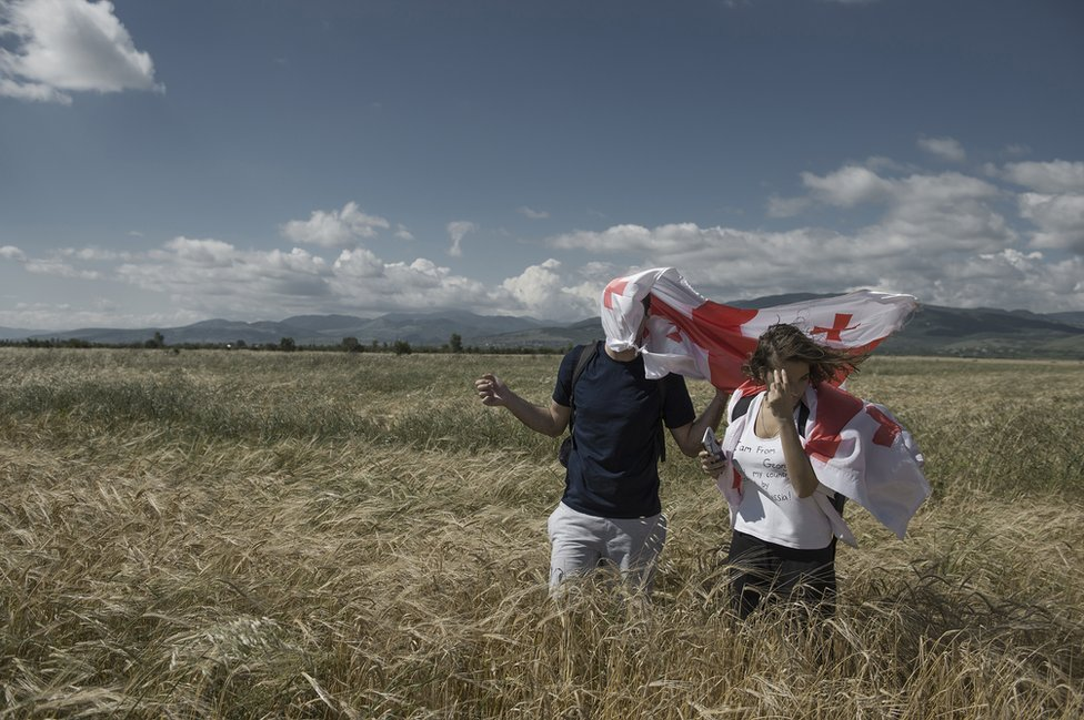 Two people walk through a field with England flags over their heads.