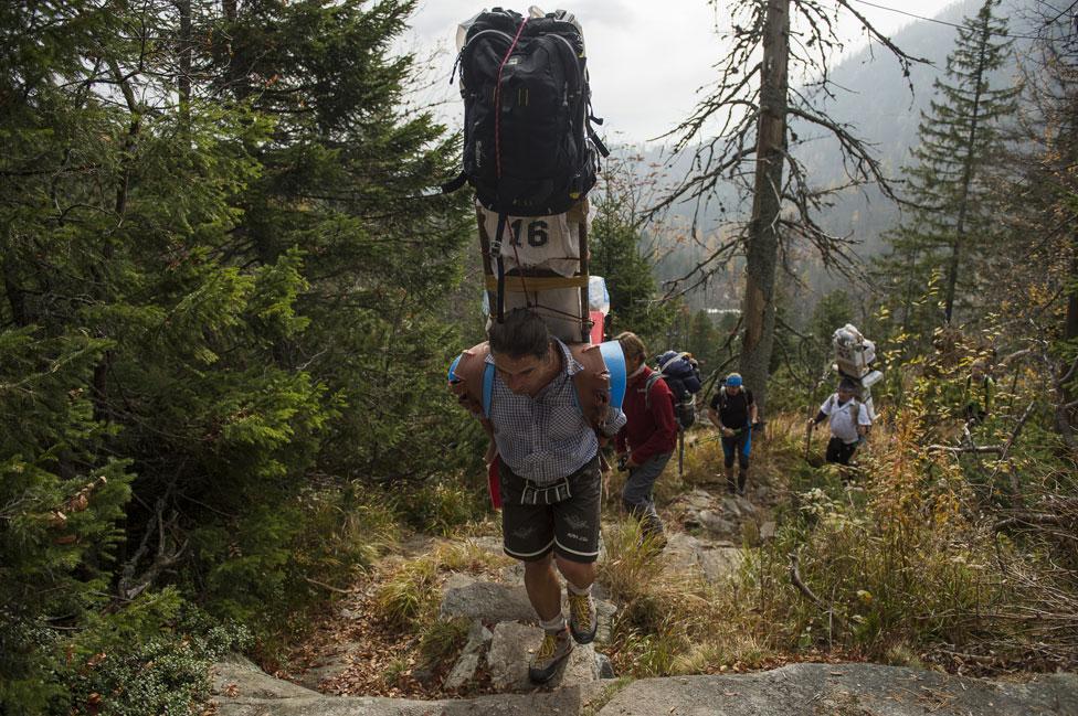 Sherpa subiendo una montaña, cargado de valijas.