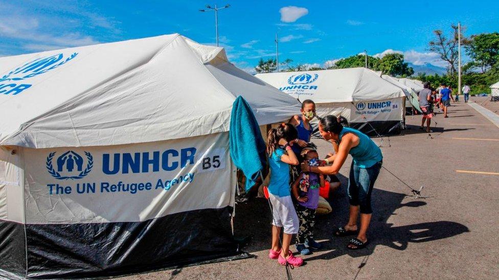 Venezuelan migrants exit a tent set up at the Tienditas International Bridge in Cucuta, Colombia, on the border with Venezuela, set up for Venezuelans who have been waiting at the Simon Bolivar International Bridge