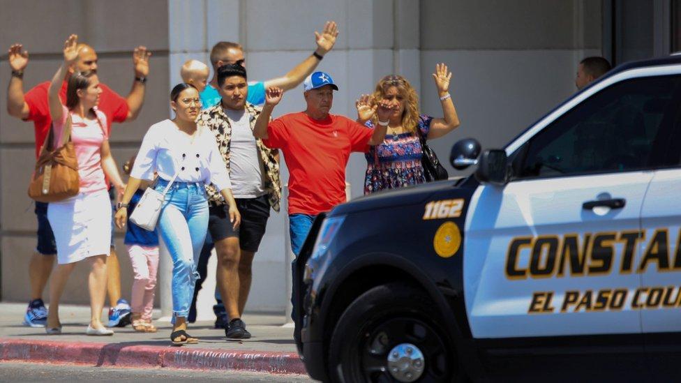 Para pelanggan Walmart keluar gedung sambil mengangkat tangan setelah penembakan massal di El Paso, Texas.