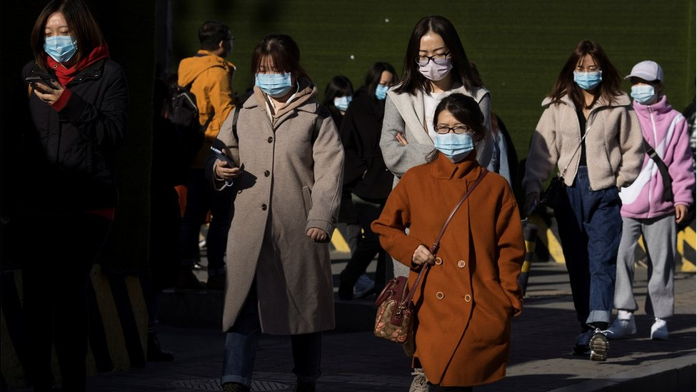 People walk in a street during morning rush hour following an outbreak of the coronavirus disease (COVID-19) in Beijing, China, November 3, 2020.