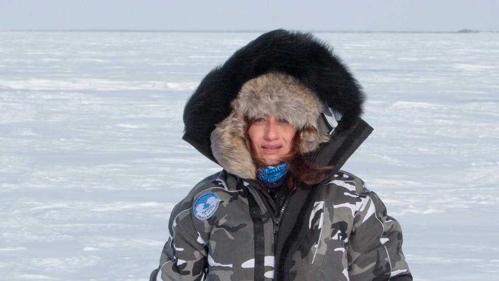 Carla Santana Torres con chaqueta y gorro para la nieve en la tundra, en medio de planicies cubiertas de hielo