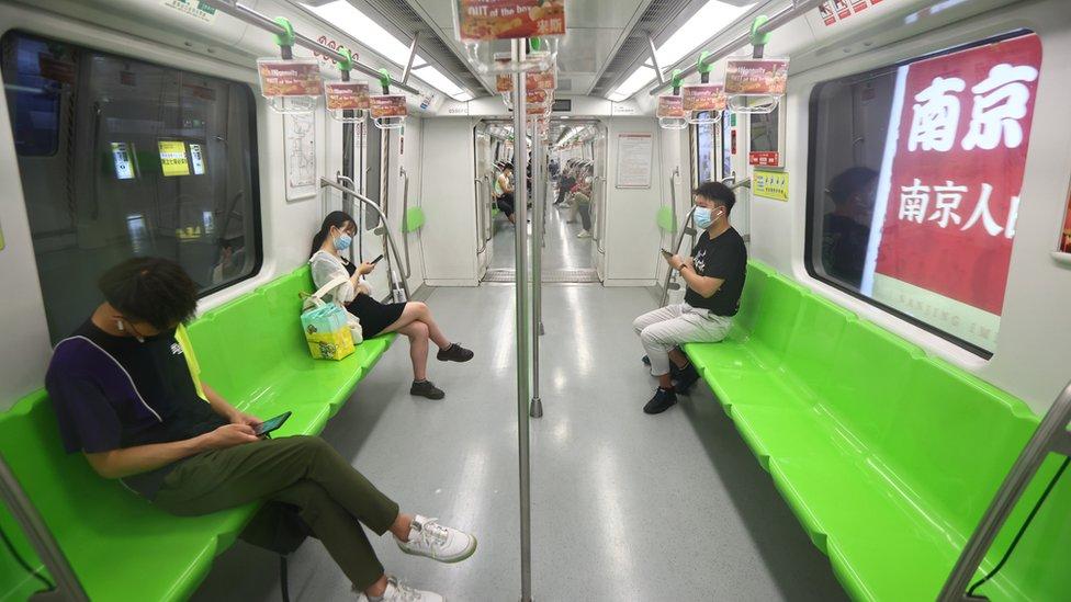 中國江蘇南京地鐵上乘客戴著口罩出行(中新社圖片27/7/2021)