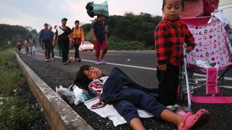 Una niña duerme sobre el pavimento mientras detrás de ella caminan migrantes provenientes de Centroamérica.
