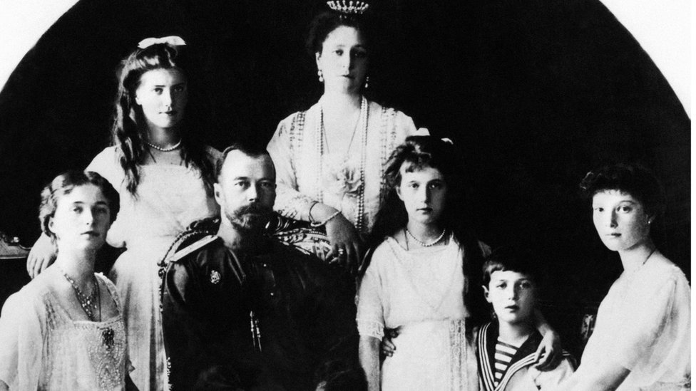 Tsar Nicholas II sits with his family - his wife, Tsarina Alexander, leans on the back of his chair and his children sit around him