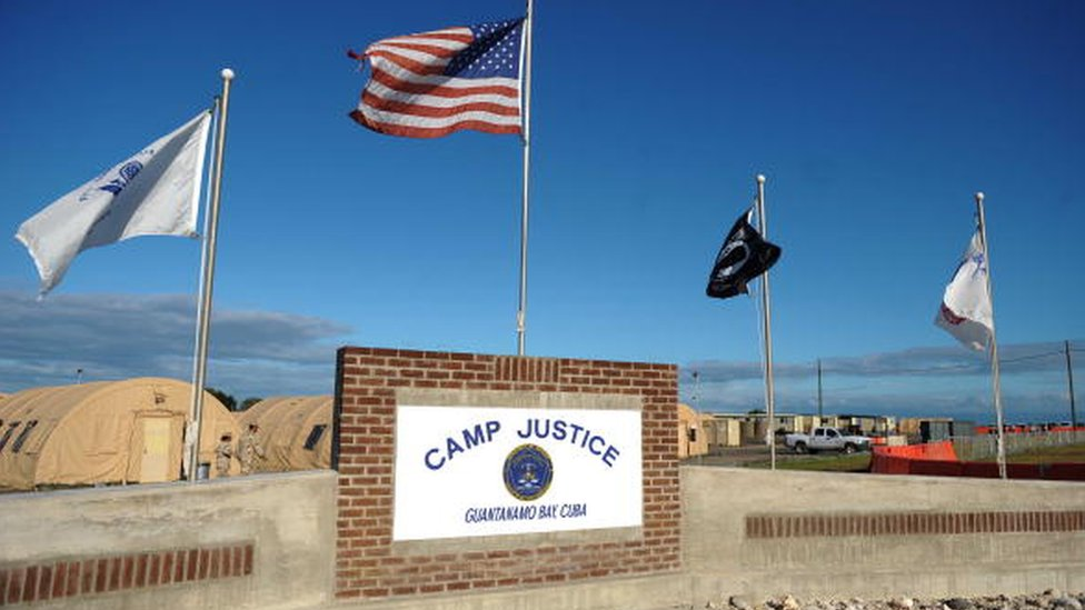 "A ""Camp Justice"" sign near the high-tech, high-security courtroom"