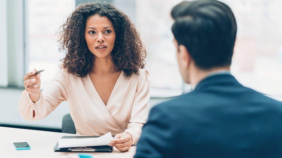 Hombre y mujer en oficina conversando.