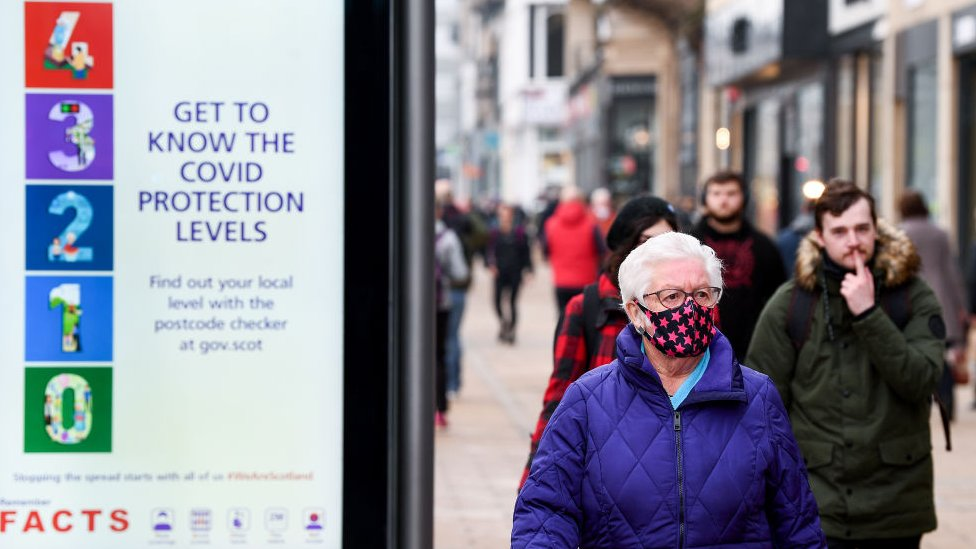 People in a street in Scotland alongside a sign on Covid protection rules