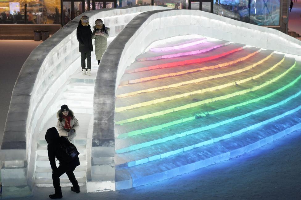 Orang-orang berjalan di jembatan es yang diterangi warna pelangi