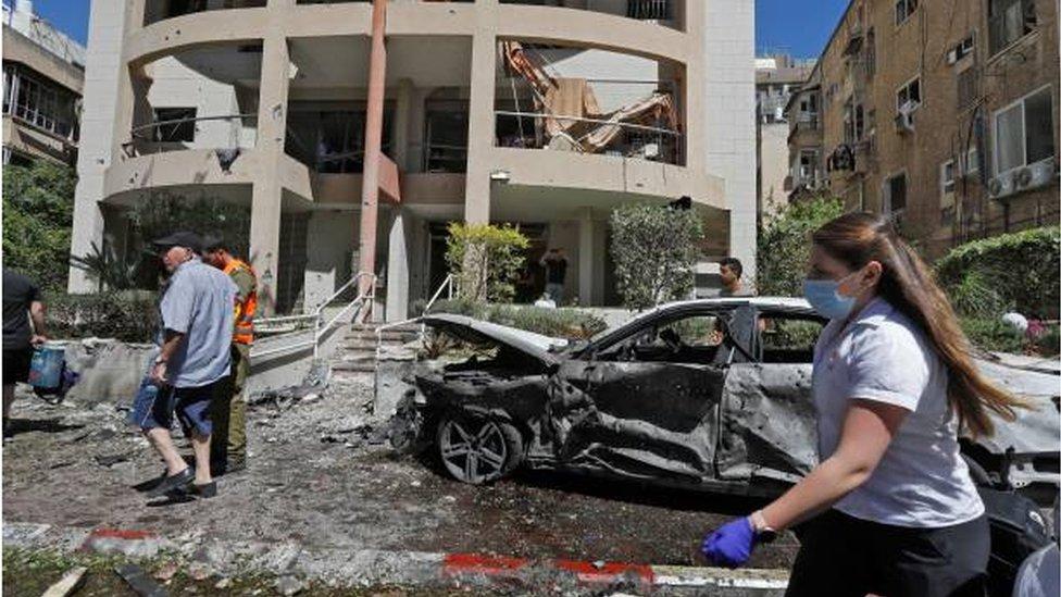 فراد من خدمة الأمن والطوارئ الإسرائيلية يعاينون موقع سقوط أحد الصواريخ التي أطلقت من غزة في مدينة رامات غان شرقي تل أبيب