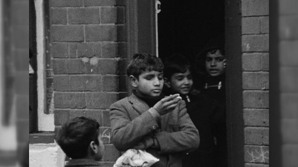Young boys gathered at a front doorway