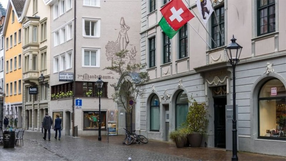 Rua de Zurique com comércios e bandeira da Suíça