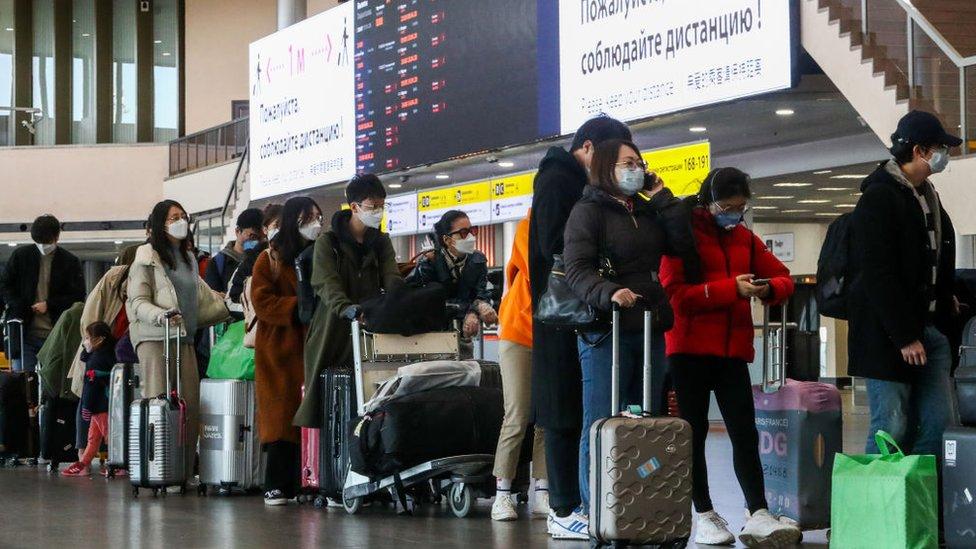 Pessoas com malas na fila no aeroporto