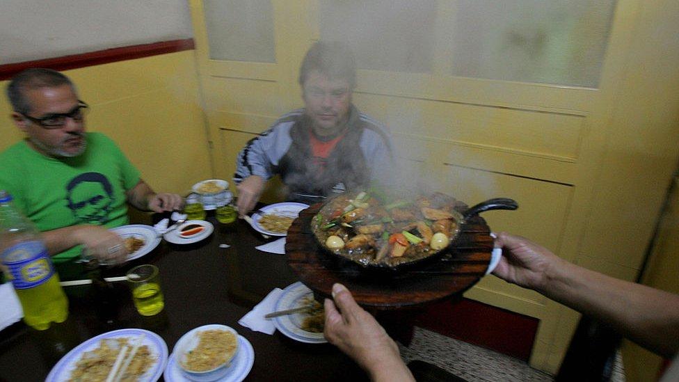 Gente comiendo en un chifa.