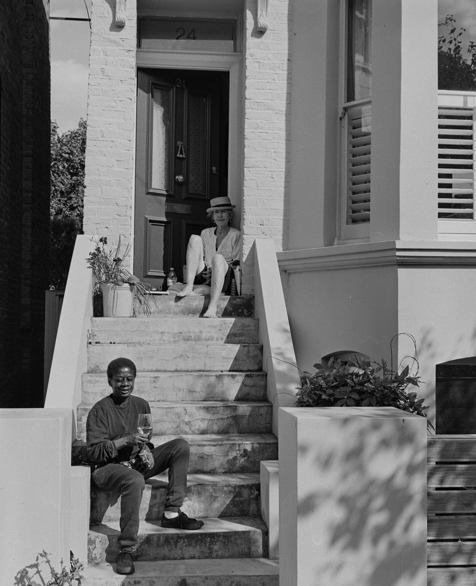 Two people sit on the steps of a residential building drinking together