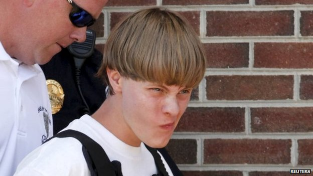 Police lead suspected shooter Dylann Roof, 21, into the courthouse in Shelby, North Carolina, 18 June 2015.