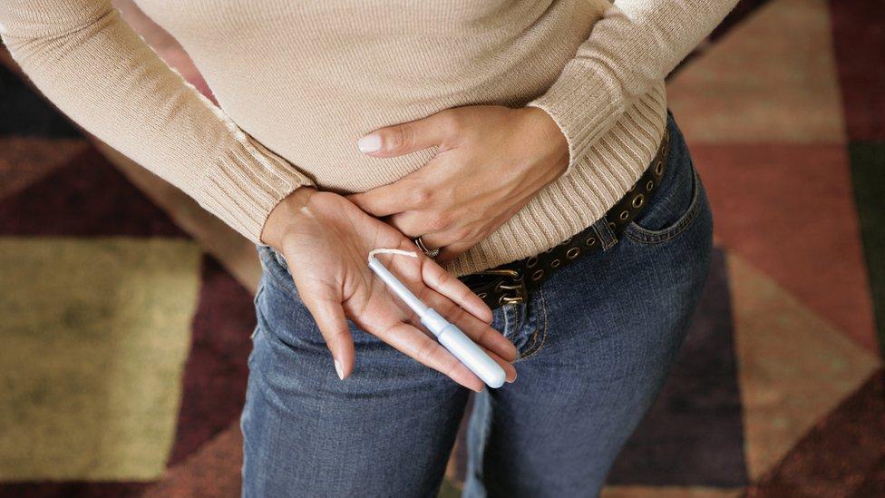 Una mujer sostiene un tampón vaginal