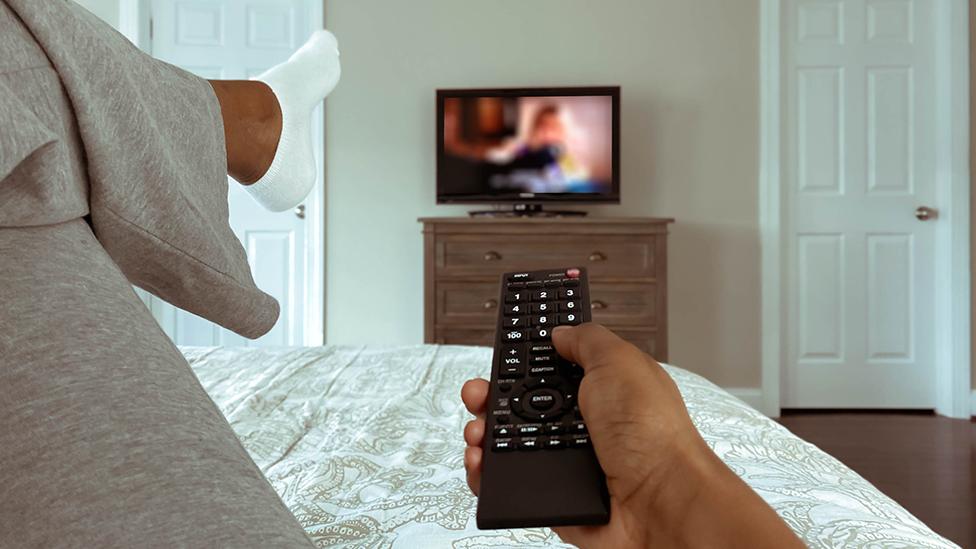 Una mujer mirando televisión desde su cama