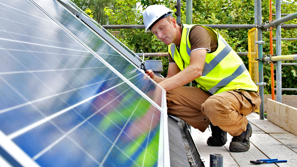 Stock image of a workman fixing solar panels to a house