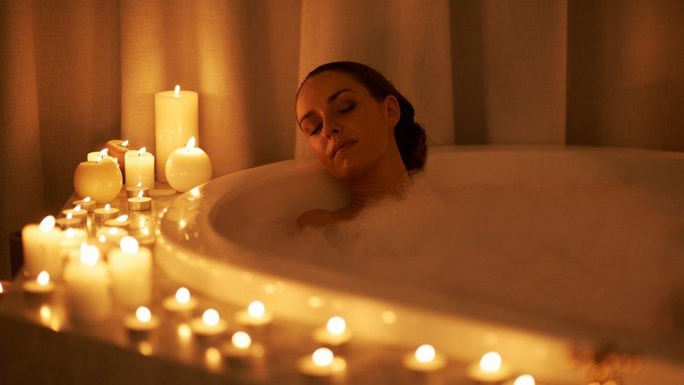امرأة تستحم على ضوء الشموع