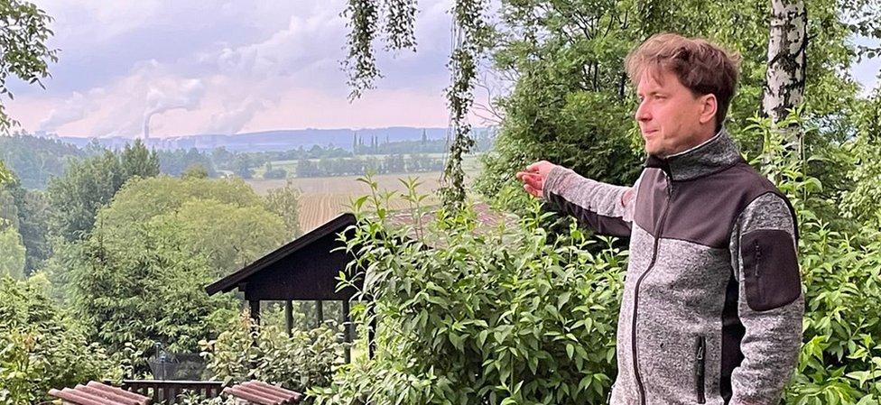 Milan Starec pokazuje na termoelektranu Turov preko granice