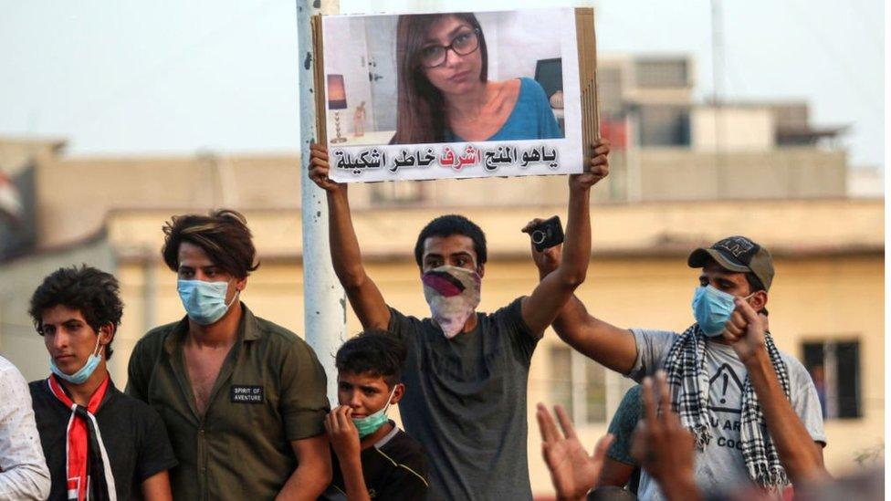Homem, alguns com máscaras, protestam - um deles mostra cartaz com foto de Mia Khalifa