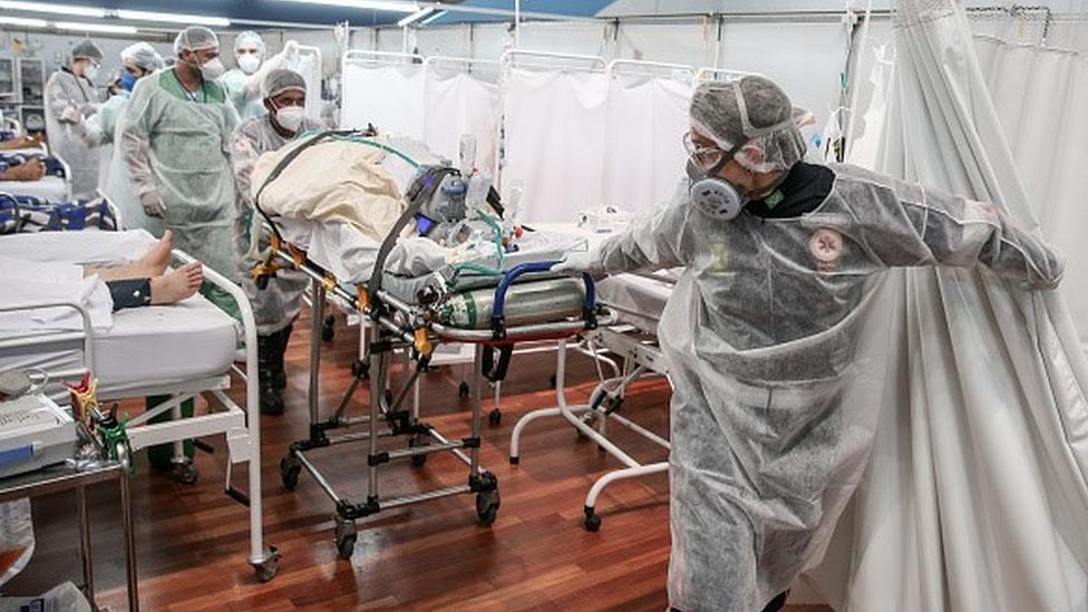 Profissionais da saúde puxam uma maca num hospital