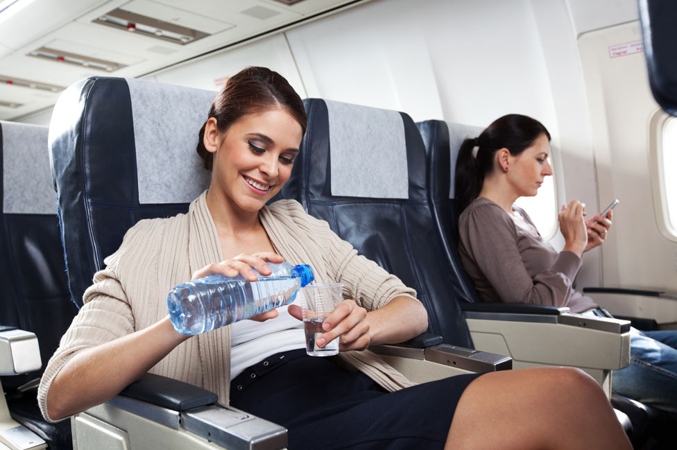Mujer bebe agua durante un vuelo