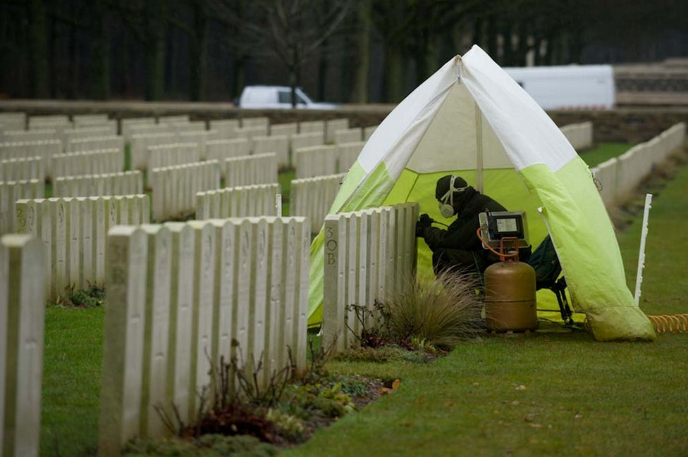 Person covered by a small tent repairing a headstone at Delville Wood Cemetery in France