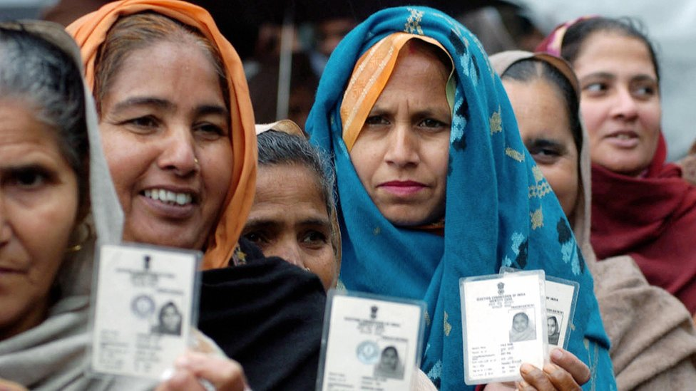 ndian village women hold up their voting cards as they await their turn to vote at a polling station in Majitha
