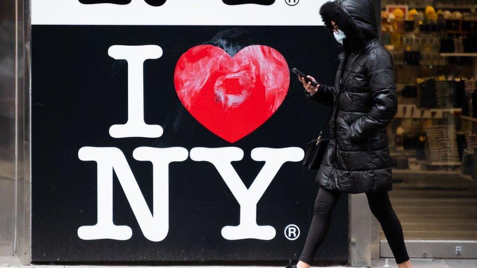 """Una mujer pasando por una señal de """"I love New York"""""""