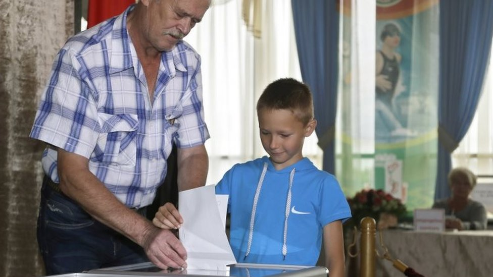 A Belarusian man casts his ballot with a boy at a polling station during parliamentary elections in Minsk (11 September 2016)