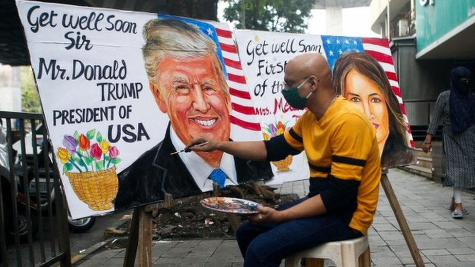 A man paints a mural of U.S. President Donald Trump and first lady Melania after they tested positive for the coronavirus on a street in Mumbai, India