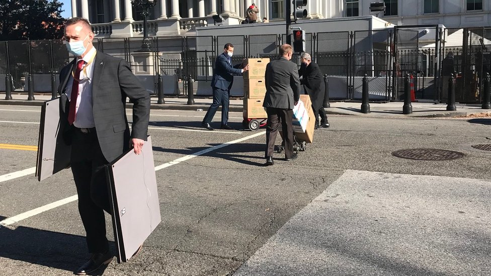 Staff carry pictures and pictures out of the White House