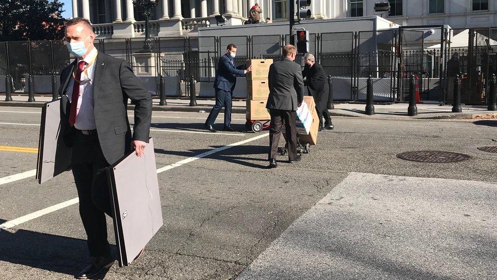 Karyawan memindahkan barang-barang