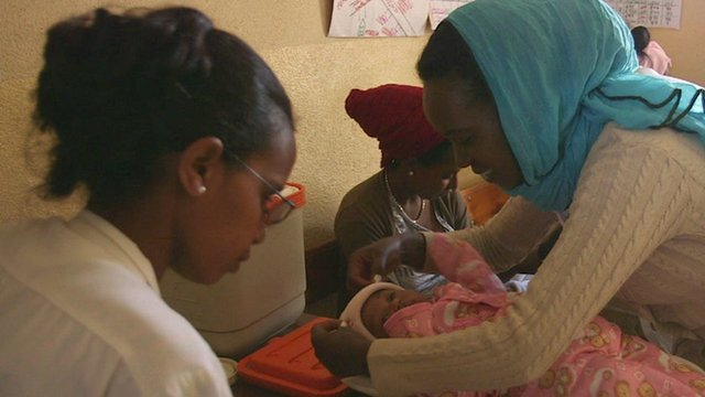 A baby being looked after by a mother and a healthcare worker