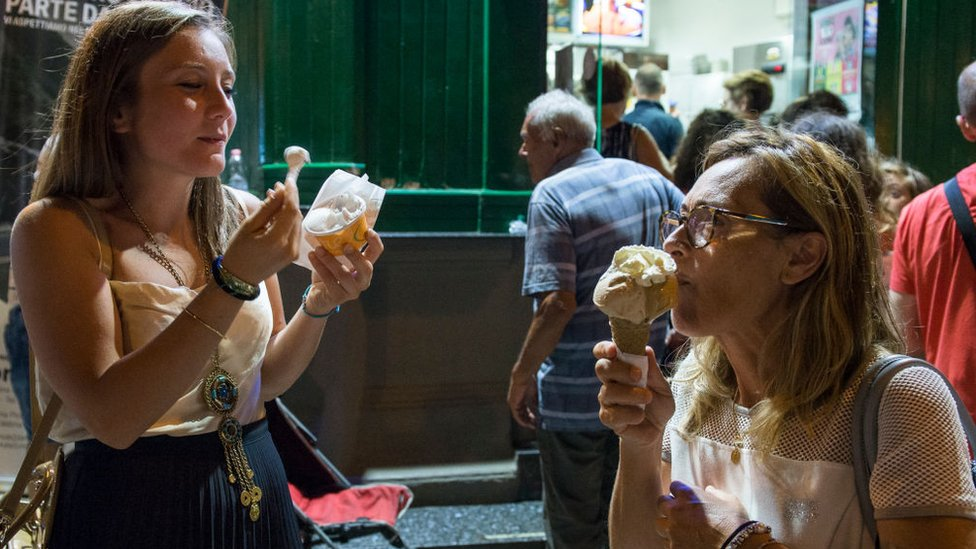 Two women eat ice cream in front of the Cesare ice cream shop in Calabria