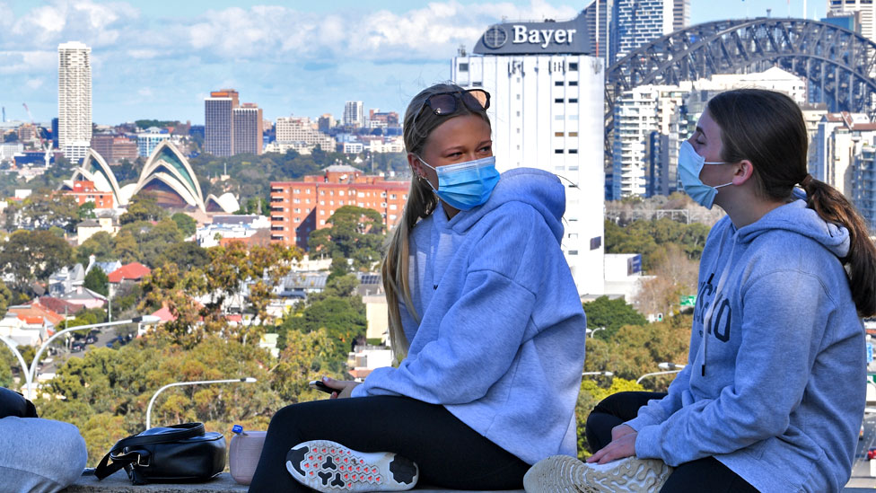 Two girls wearing face masks sit above the Bradfield Highway in the suburb of North Sydney with the city in the background on July 07, 2021 in Sydney, Australia.