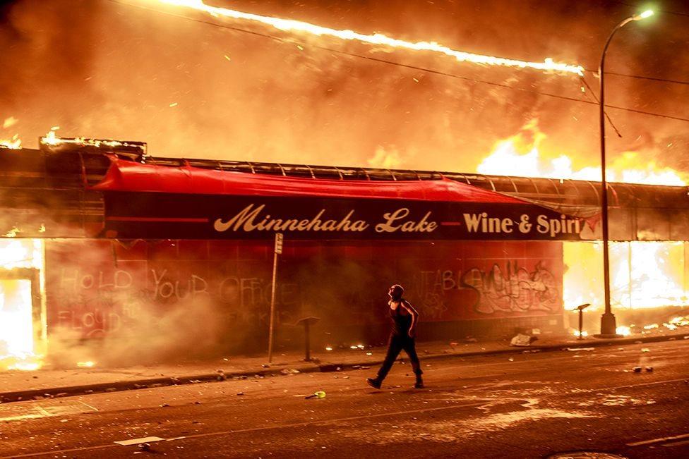 Seorang demonstran berjalan di sebelah toko yang terbakar di Amerika Serikat.