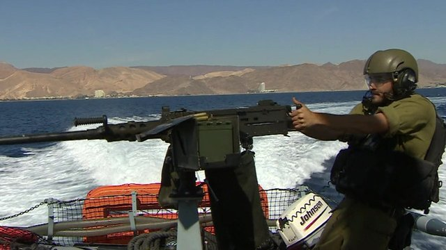 Israeli soldier on a boat with a gun