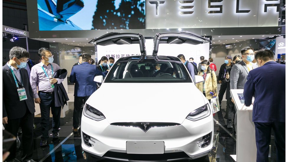 People view a Tesla Model 3 electric car at the auto exhibition area of the third International Import Expo in Shanghai, China, Nov. 6, 2020.