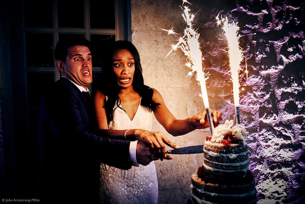 Una pareja cortando su pastel de bodas con luces