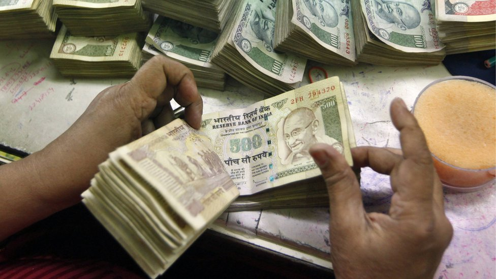 An employee counts Indian currency notes at a cash counter inside a bank