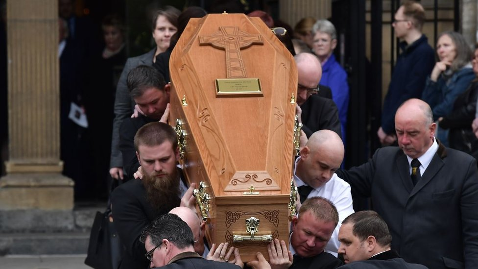 Mourners watch as the coffin of journalist Lyra McKee is taken out of the church after the funeral at St Anne's Cathedral on 24 April 2019 in Belfast, Northern Ireland.