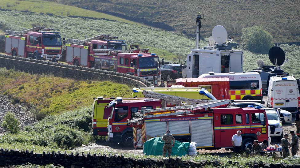 Fire engines park up on the moor as firefighters continue tackling a blaze on Saddleworth Moor